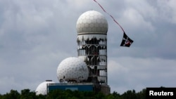 A kite flies near the antennas of a former U.S. National Security Agency Cold War listening post at Teufelsberg hill in Berlin.