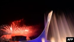 Russia -- Sochi - Fireworks explode behind the Olympic flame claudron after it was extinguished at the end of the Closing Ceremony of the Sochi Winter Olympics outside the Fisht Olympic Stadium on February 23, 2014. AFP PHOTO / YURI KADOBNOV