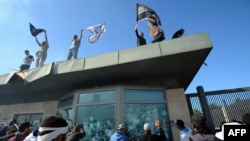 Tunisian protesters break windows as they hold Islamic flags above the gate of the U.S. Embassy compound in Tunis during a protest against the film on September 14.