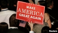 U.S. -- A Trump supporter holds up a campaign sign at Republican U.S. presidential nominee Donald Trump's election night rally in Manhattan, New York, U.S., November 9, 2016