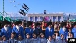 Түркімен ұлттық костюмдерін киген адамдар Ашғадаттың орталық алаңында мерекелік шараға жиналды. Түркіменстан, 22 наурыз 2012 жыл. (Көрнекі сурет)