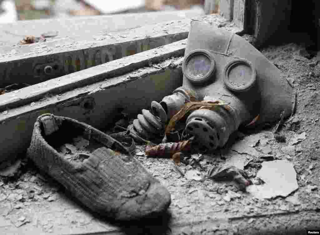 Жас баланың газтұтқысы мен аяқ киімі. Чернобыль атом электр станциясы маңындағы иен қалған Припят қаласы. 4 сәуір 2011 жыл.