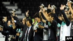 South Korean players and coach Cho Kwang-Rae (C) celebrate after beating Uzbekistan in their 2011 Asian Cup football match for third place at Al-Sadd Stadium in the Qatari capital Doha on January 28, 2011