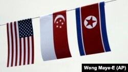 U.S., Singaporean, and North Korean flags decorate the entrance of a local bar in Singapore.