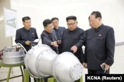 Солтүстік Корея басшысы Ким Чен Ын (ортада) ядролық қарудың макетін қарап тұр. Ресми сурет.