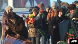 Relatives mourn over the coffin of a victim of the Perm nightclub fire