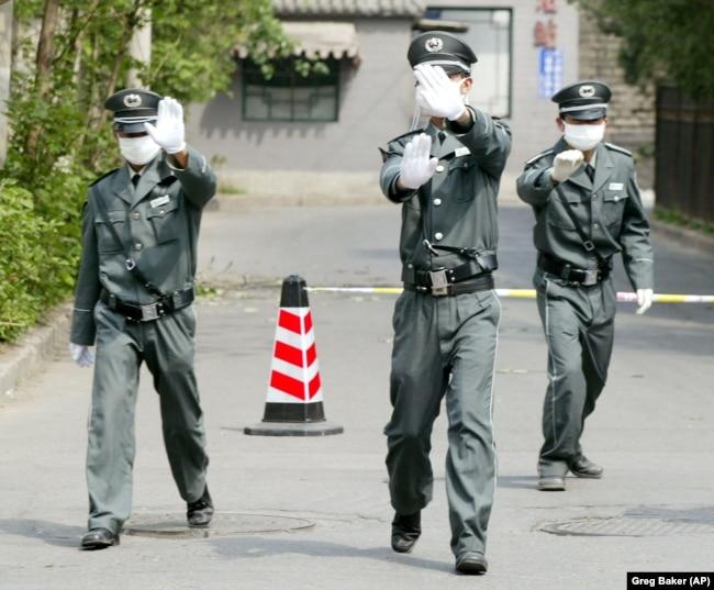 Personeli i sigurisë tenton të parandalojë fotografimin jashtë një spitali në Pekin, në prill të vitit 2003.