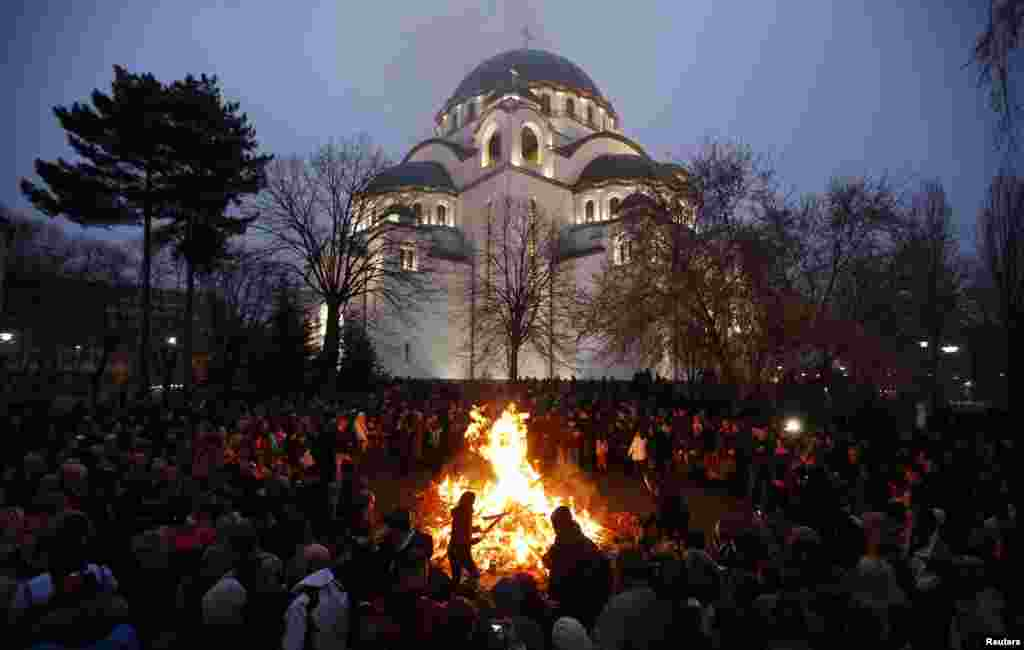 In Serbia, believers burn dried oak branches, which symbolize the Yule log, on Orthodox Christmas Eve in front of the St. Sava temple in Belgrade.