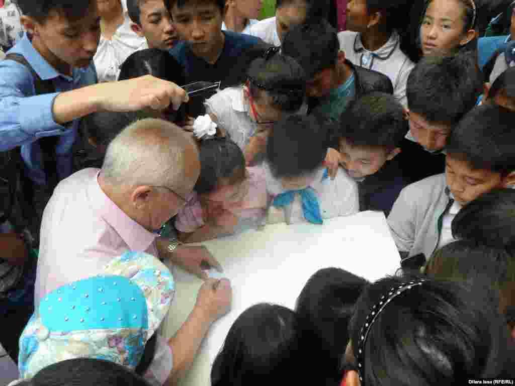 Орталық саябақта суретші Расул Естемесов (ортада) өткізген шеберлік сабағына қызығушылық танытқан балалар оны қаумалап алды. Шымкент, 14 мамыр 2016 жыл.