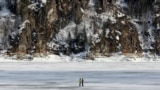 A couple walks on spring ice on the frozen Yenisei River outside Krasnoyarsk, Russia. (Reuters/Ilya Naymushin)