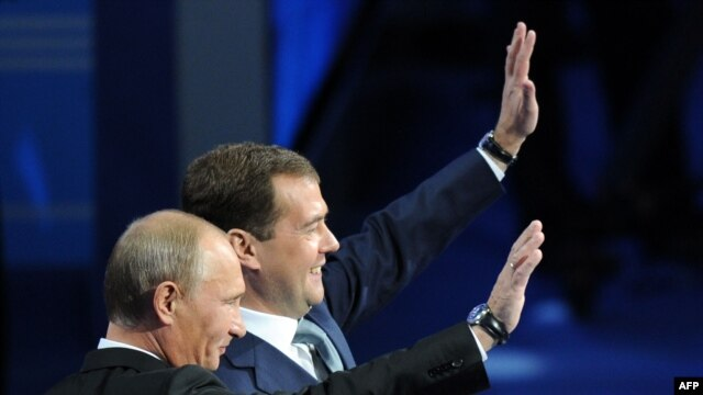 Russian Prime Minister Vladimir Putin (nearer, left) and President Dmitry Medvedev wave to attendees at a United Russia party congress in Moscow on September 24.