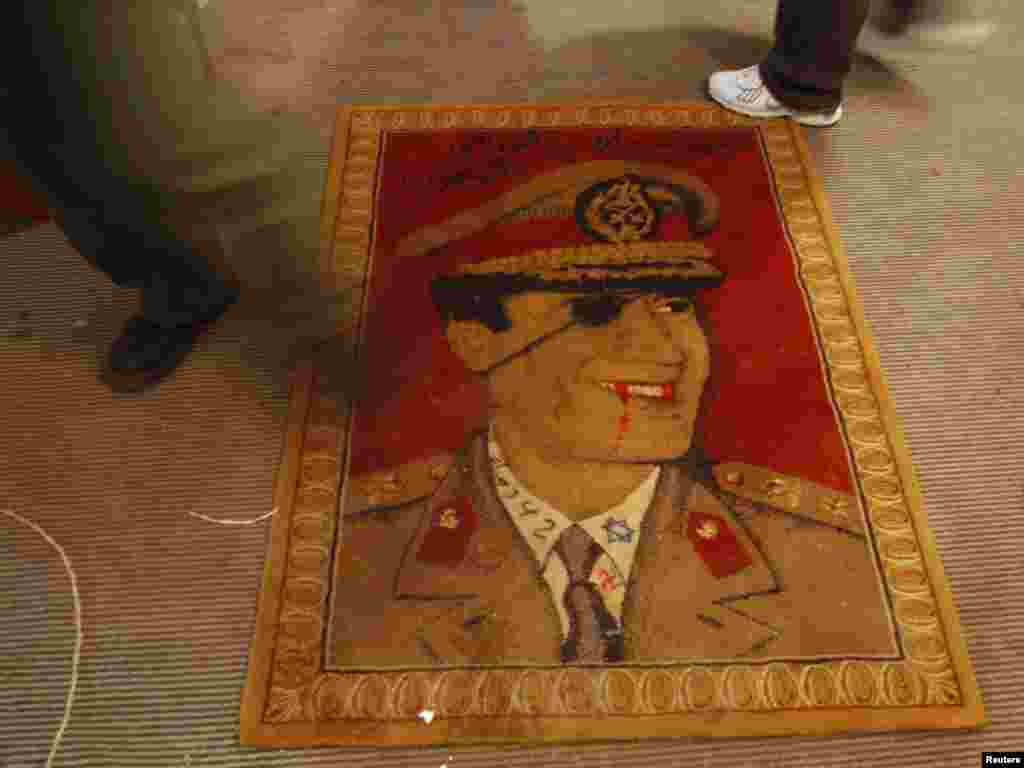 A protester walks over a rug depicting a defaced portrait of Libyan leader Muammar Qaddafi in Benghazi. Photo by Suhaib Salem for Reuters