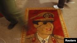 ლიბიაში დემონსტრანტები აბიჯებენ ხალიჩას მუამარ კადაფის გამოსახულებით