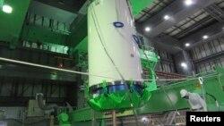 Рабочие вынимают из бассейна четвертого энергоблока АЭС «Фукусима» контейнер с отработанным ядерным топливом. 18 ноября 2013 года.