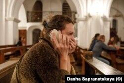 O femeie vorbește la telefon în timp ce trupele OMON blocaseră toate ieșirile din biserică.