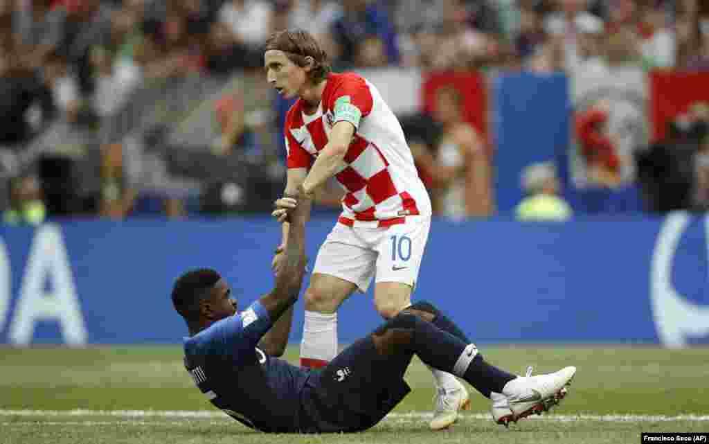 Хорват Лука Модріч допомагає встати французькому гравцеві Самуелю Умтіті під час фінального матчу