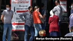 People wait outside a pharmacy in Almaty on July 8.