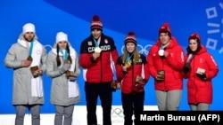 Призеры Олимпийских игр в Пхёнчхане в дисциплине дабл-микст в кёрлинге. Слева в серой форме – Александр Крушельницкий и Анастасия Брызгалова.