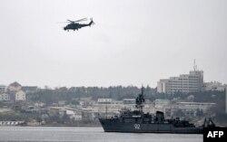 Российский военный вертолет кружит над портом в Севастополе.