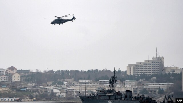 """Ukraine -- A Russian Mi24 military helicopter flies over the Russian navy minesweeper ship """"Turbinist"""" in the harbor of Sevastopol, March 7, 2014"""