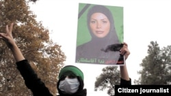 An opposition supporter holds a picture of Neda Agha Soltan at an anti-government demonstration in 2009.