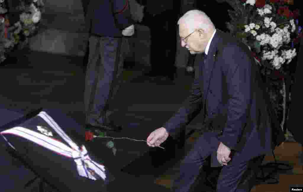 Current Czech President and Havel's longstanding political rival Vaclav Klaus places a flower in front of the late leader's coffin inside Prague Castle.