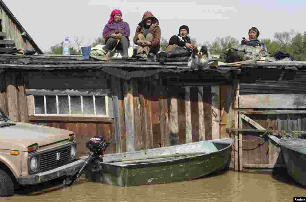 Local residents wait on the roof of houses surrounded by floodwaters in the settlement of Ust-Charish in Russia's Altai region, on June 3. (Reuters/Andrei Kasprishin)
