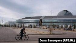 Астанадағы EXPO-2017 халықаралық көрмесінің бас ғимараты жанынан велосипедпен өтіп бара жатқан адам.