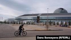 Мужчина едет на велосипеде мимо основного здания выставки EXPO-2017.