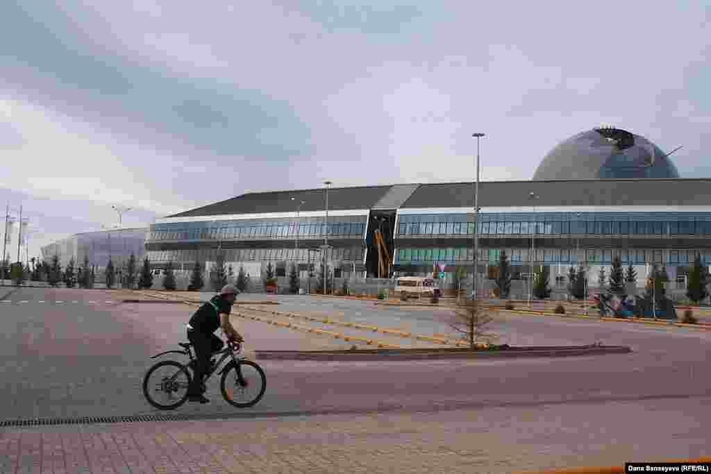 Мужчина едет на велосипеде мимо основного здания EXPO 2017.