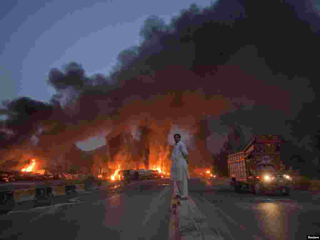 A local watches fuel tankers burn from a median along the GT road in Nowshera, in Khyber Pakhtunkhwa Province, in October 2010.
