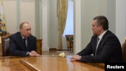 Russian President Vladimir Putin (left) meets with Crimean leader Sergei Aksyonov at the Novo-Ogaryovo state residence outside Moscow on April 14, where he named him acting governor.