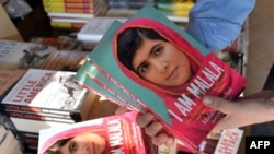 A bookstore employee poses with copies of the memoirs of Pakistani child activist Malala Yousafzai in Islamabad.