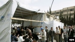 Iraqi refugees line up at a UNHCR registration center in Syria