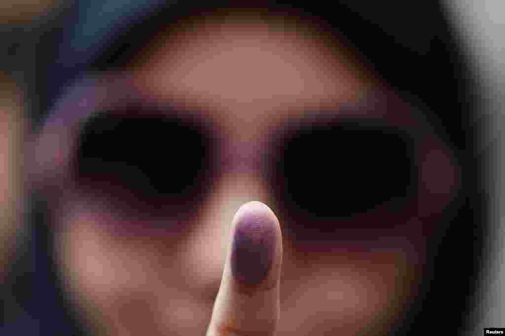 Voter Zeynab shows the ink stain on her finger, to prove that she has voted, outside the Iranian Consulate in central London. (Reuters/Stefan Wermuth)