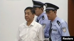Полицейские ведут в зал суда бывшего высокопоставленного китайского политика Бо Силая. Чунцин, 22 августа 2013 года.