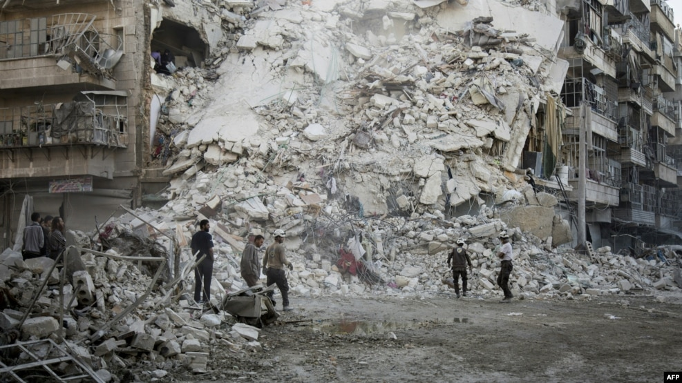 Members of the Syrian Civil Defense, known as the White Helmets, search for victims amid the rubble of a destroyed building following reported air strikes in the rebel-held Qatarji neighborhood of the northern city of Aleppo on October 17.