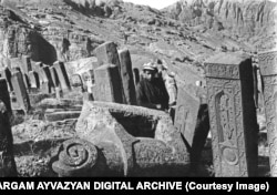 A young man poses among khachkars and a stone ram in the Julfa cemetery in 1915.