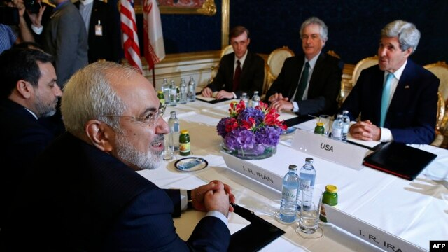 Iranian Foreign Minister Mohammad Javad Zarif (left) meets with U.S. Secretary of State John Kerry (right) during talks between the foreign ministers of the six powers negotiating with Tehran on its nuclear program in Vienna on July 13.