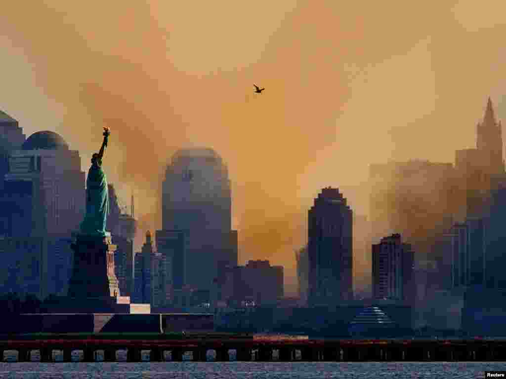 Smoke from the remains of New York's World Trade Center shrouds lower Manhattan as a lone seagull flies overhead in a photograph taken across New York Harbor from Jersey City, New Jersey September 12, 2001. Each of the twin towers were hit by hijacked airliners and collapsed in one of numerous acts of terrorism directed at the United States on September 11, 2001. REUTERS/Ray Stubblebine