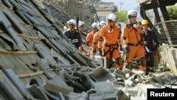 Fotografi e sotme ku shihen zjarrfikësit në veprim afër shtëpive të shkatërruara nga tërmeti në Japoni