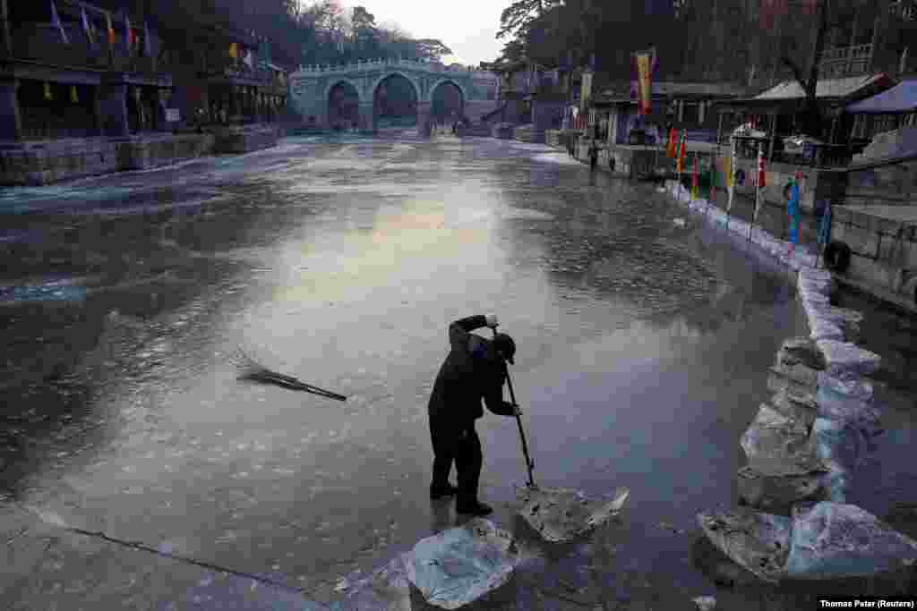 A worker removes ice in a canal in a park at the Old Summer Palace in Beijing. (Reuters/Thomas Peter)