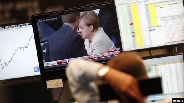 A trader at the Frankfurt stock exchange watches a news broadcast showing German Chancellor Angela Merkel. (file photo)