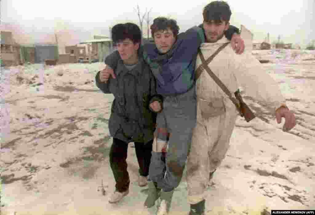 Російські війська продовжують інтенсивні бомбардування і ракетні обстріли Грозного. У чеченських бійців на озброєнні були тільки кулемети і гранати. Дуже багато загиблих і поранених. Два бійці виводять з центру міста на околицю пораненого товариша. 25 грудня 1994 року
