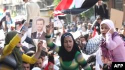 جمعيت چند هزار نفره جوانانی که در مرکز شهر دمشق گردآمده بودند، شعار می دادند: «استعمارگران گوش کنيد: سوريه هيچگاه به زانو در نخواهد آمد » و يا شعار می دادند « خدا، سوريه، بشار».(عکس:AFP)