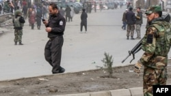 Afghan security forces stand guard after a gun attack in Kabul on March 6.