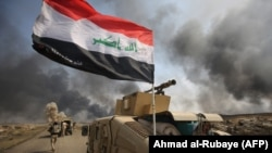 Iraqi forces hold a position as they advance toward the Islamic State group's stronghold of Hawija on September 30.