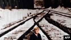 Канцлер ФРГ Ангела Меркель на фоне исторической фотографии Освенцима