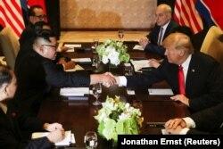 АҚШ президенті Дональд Трамп пен Солтүстік Корея басшысы Ким Чен Ын келіссөзде қол алысып отыр. Сентоса аралы, Сингапур. 12 маусым, 2018 жыл