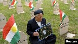 أب يحمل صورة ابنه في مقبرة لضحايا حلبجة